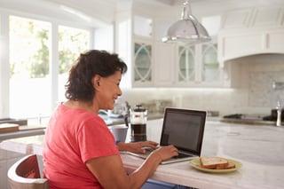 An Hispanic woman working on a laptop